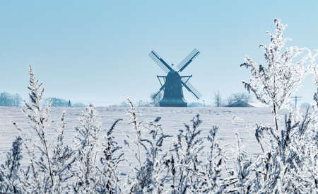 Snowy winter landscape with a historic windmill in the climate commune of Saerbeck Sinningen, Germany