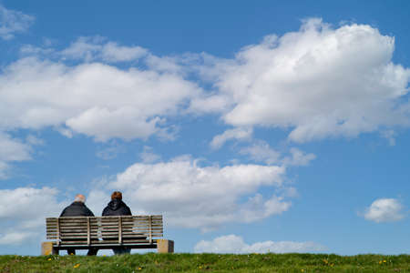 Mature couple sitting on a bench and looking into the distance Standard-Bild