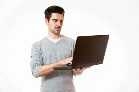 tage: A young man works on a laptop while standing Stock Photo