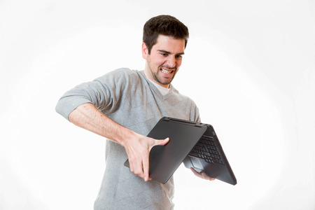 tage: A young tries to break a laptop the other way around Stock Photo