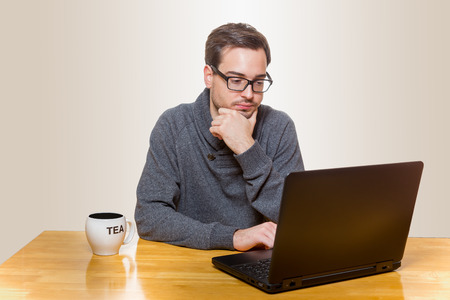 tage: Man sitting on a table working on a laptop and drinking tea