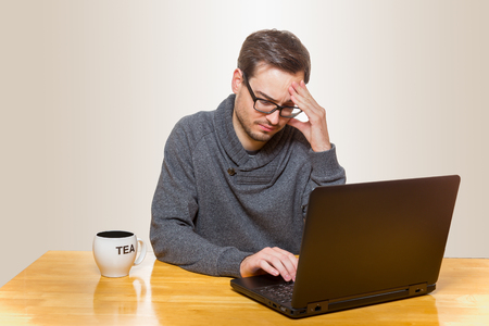 tage: Man sitting on a table working on a laptop and touching his forehead Stock Photo