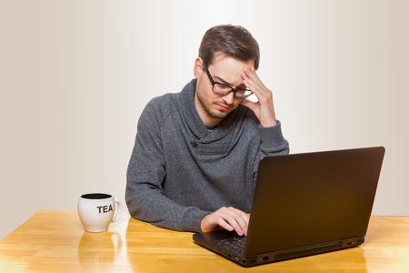 Man sitzt auf einem Tisch auf einem Laptop arbeiten und berührte seine Stirn Standard-Bild - 52187463