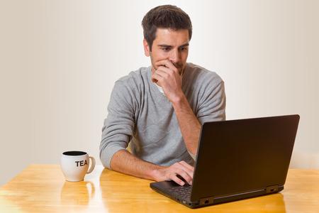 Man sitzt auf einem Tisch auf einem Laptop und Tee trinken Standard-Bild - 52187501