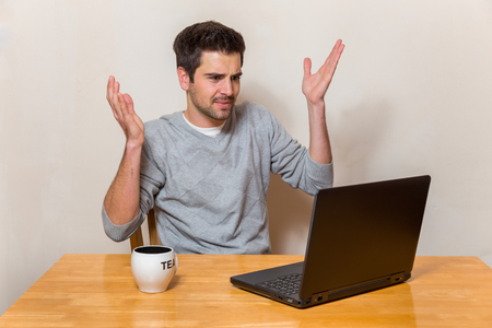 tage: Man got problems with his laptop while sitting on a table Stock Photo