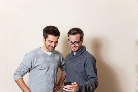 tage: Two happy men are looking on one cellphone Stock Photo