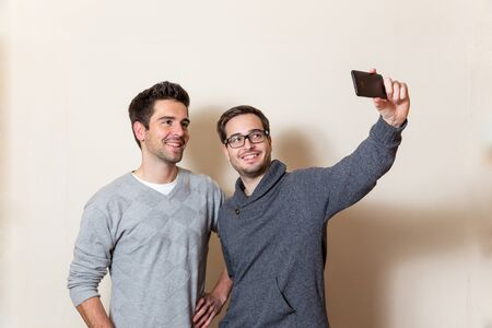 tage: Two smiling men are doing a self portrait with a cellphone Stock Photo