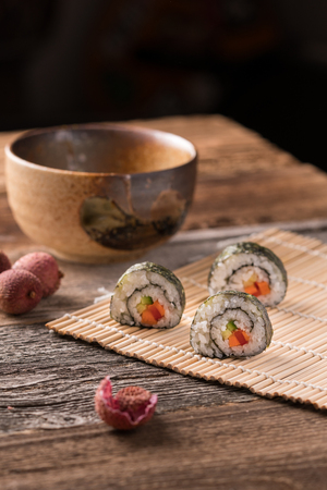 Three maki sushi rolls on bamboo mat on wooden table, traditional asian tee bowl, lychee and lychee peel - angled view, blurred background, vertical format, cutout 写真素材