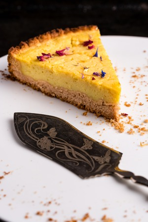 One piece of vegan lemon cheesecake, garnished with eatable petals, on a white plate with ornate cake server and some crumbs - close-up, vertical portrait orientation
