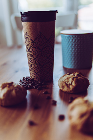 Breakfast on the go for the commute: Coffee to-go and three homemade vegan bread rolls, decorated with roasted coffee beans and teal ceramic can (focus on beans and cup, vertical)