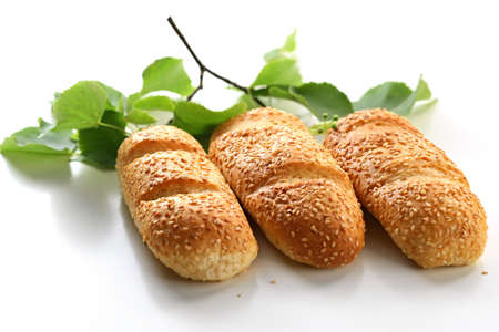 Three bread rolls with birch leaves on background