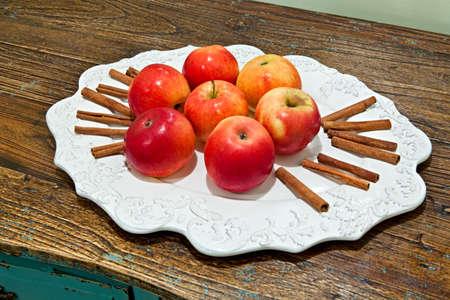 シナモンスティックと白い皿に 7 つの赤いリンゴ 写真素材