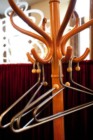 Wooden Coat rack with metal hangers in little French restaraunt