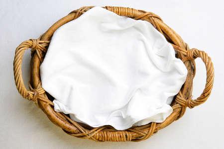 canasta de pan: Vista desde arriba, la cesta de panadería con la servilleta sobre el mantel blanco