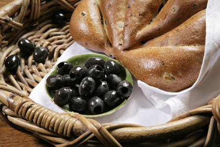 Chiabatta with black olives in the bakery basket Stock Photo