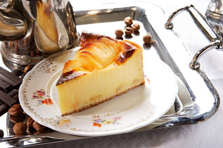 flan: Pear flan on porcelian plate with silver tray and pot