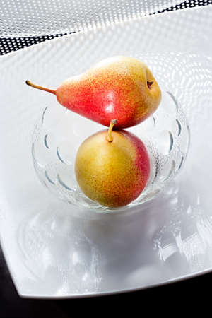 Two appetizing pears on the white glass plate Stock Photo
