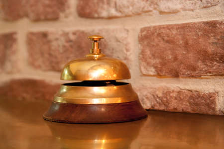 Service bell at an hotel reception in front of break wall photo