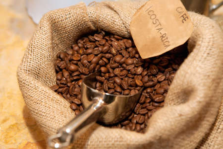 Sacks of roasted flavoured coffee beans with metal scoop and paper label