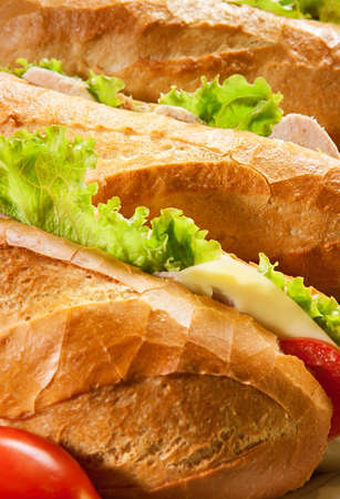Three big sandwiches with chicken and with cheese and tomatoes