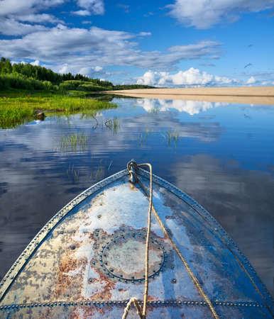 夏の雲と美しい湖でボートでの金属の船首