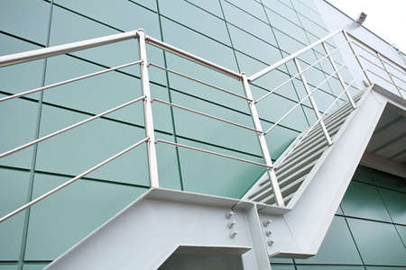 Outdoor Metal staircase on the wall of modern industrial building Stock Photo