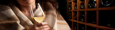 Glass of wine in womans hands on wooden wine rack background