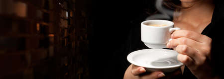 Cup of coffee on black background in womans hands Stock Photo