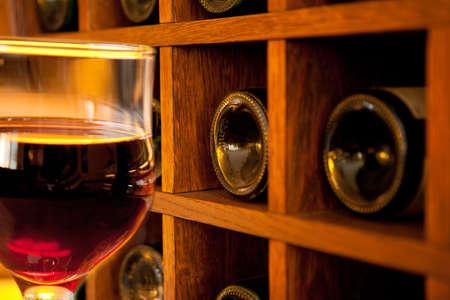 Glass of wine on wooden wine bottles rack background Stock Photo
