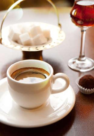 一杯のコーヒー テーブルの上。キャンディ、ワイングラス、砂糖