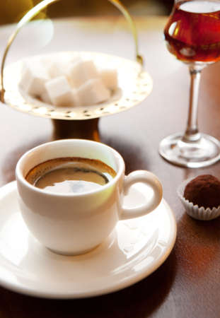 Cup of coffee on a table. Candy, wineglass and sugar
