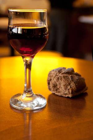 デフォーカスでパンを持つテーブル上にワインのガラス 写真素材