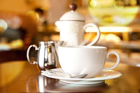 スプーン、クリーム、コーヒーのポットとテーブルの上のコーヒー カップ