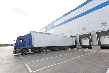 Big entrepôt de distribution avec des portes pour les charges et camion bleu