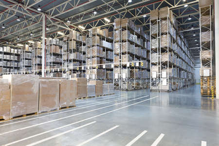 Huge distribution warehouse with boxes on high shelves Stock Photo