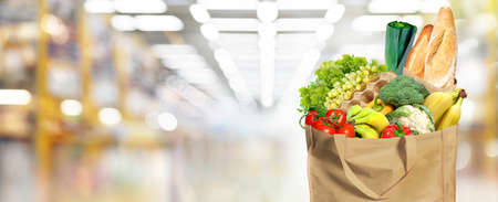 Eco-friendly reusable shopping bag filled with different fruits, vegetables and bread. Supermarket background in blur.