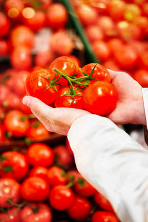 Man holding a bunch of fresh tomatoes on the background of shelved red tomatoes 版權商用圖片