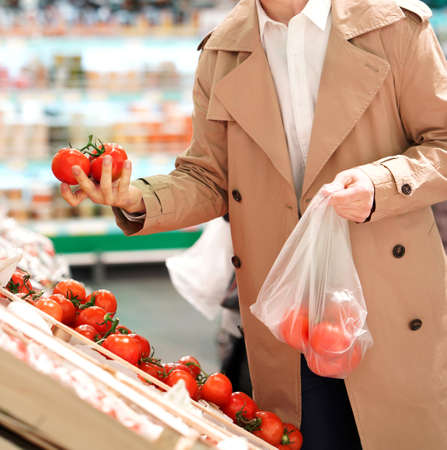 Man picks fresh tomatoes in a supermarket. Man holding a bunch of fresh tomatoes in the right hand and bag with tomatoes in the left hand