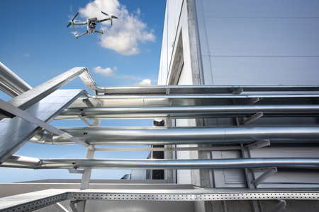 Equipment monitoring by Drone over Large Pipes of ventilation system against the blue sky. 版權商用圖片