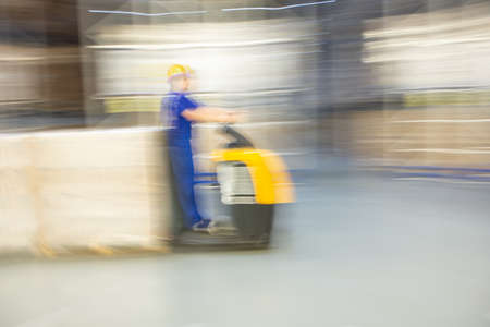 A worker of forklift is moving in a huge distribution warehouse. Blurred background dynamically moving. Imagens