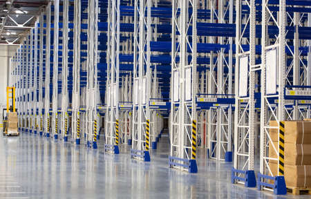 Perspective of Huge distribution warehouse with high empty shelves and forklift. Bottom view.