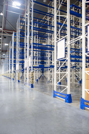 Perspective of Huge distribution warehouse with high empty shelves. Bottom view. 版權商用圖片