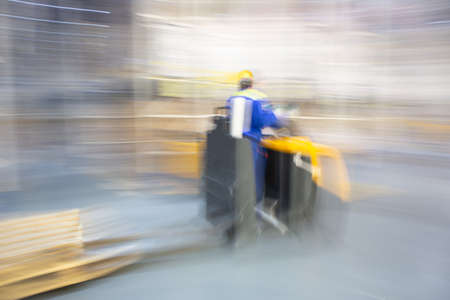 A worker of forklift is very fast moving in a huge distribution warehouse. Blurred dynamically moving background.
