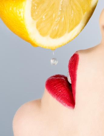 Beautiful lips and falling drop of lemon  免版税图像