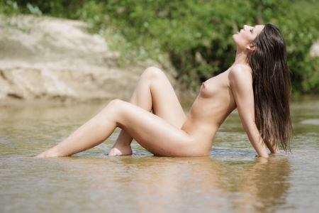 naked young women: Beautiful naked woman in water  Stock Photo