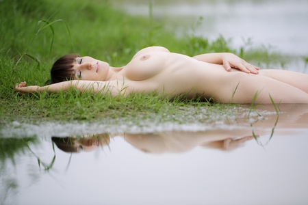Beautiful naked woman and reflection in water
