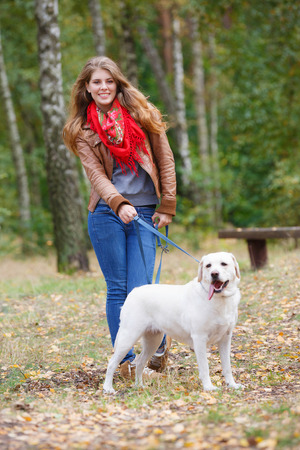 Beautiful woman walking with her dog in the forest  Foto de archivo