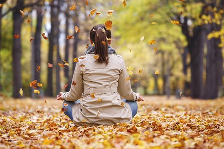 Woman meditator in the autumn park