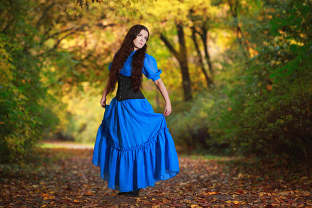 A beautiful woman in a blue dress in autumn park  photo