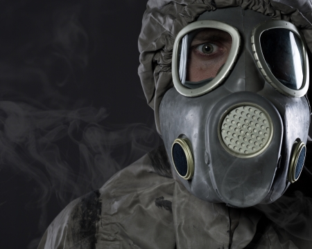 The man in a gas mask in smoke  photo